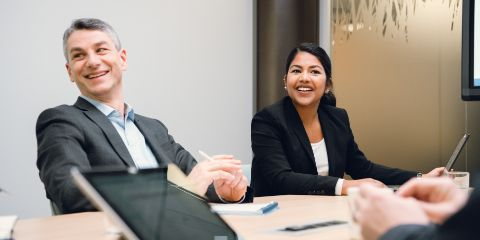 An experienced man and a young woman are sitting together at a table in a meeting room and laughing in a relaxed manner.