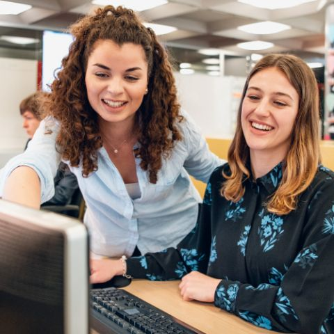 Two female commercial school interns are discussing something together at a workstation. In doing so, the dark-haired young woman is showing her light-haired female colleague something on the screen.