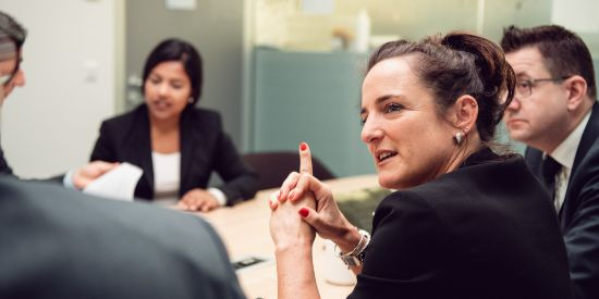 A dark-haired woman is explaining something to her male colleague at a conference table.
