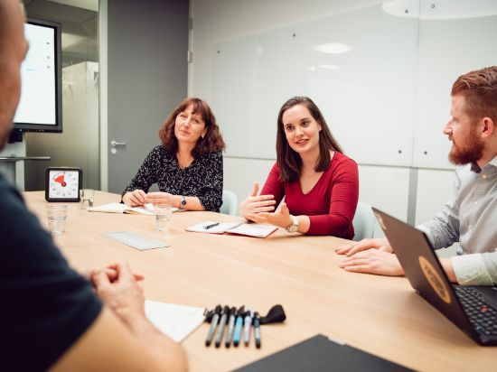 A young female IT professional is explaining something to her male colleagues and one female colleague. They are sitting at a large table, a Time Timer is visible in the background.