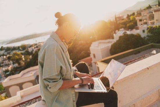 Woman sitting with a laptop on her balcony at sunset with a view of the city.