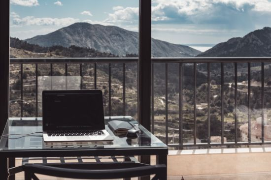 Laptop in front of a panoramic window overlooking the hill.